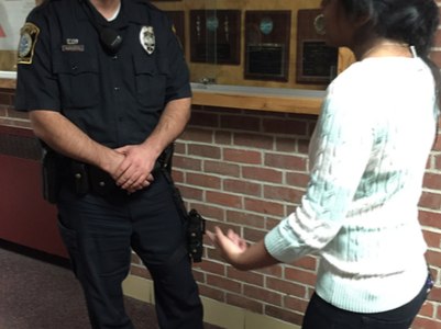 Police force-- Officer Ferrik Mustafai and senior Niki Patel discuss issues in the hallway. Mustafai took over the position of SRO after Joanna Blumetti returned to the patrol division.