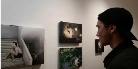 Life imitates art-- 2015 alumni Omar Taweh observes his photography on the walls in the Tunxis Community College Art Show.
