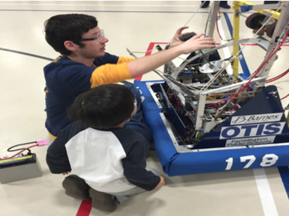 Shooting for inspiration--Senior Matt Scalzo works with an elementary school student showing him all of the parts of Captain Falcon, the team's 2014 robot, in addition to how the robot functions by punching the giant ball to score points in the game.
