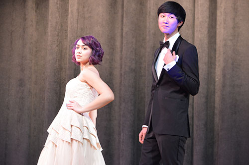 Show off those smiles-- Junior Jillian Maraj and senior Danny Ha pose at the end of the runway and display several prom themed designs. All models' makeup was done by LaBelle Chateau before the show.