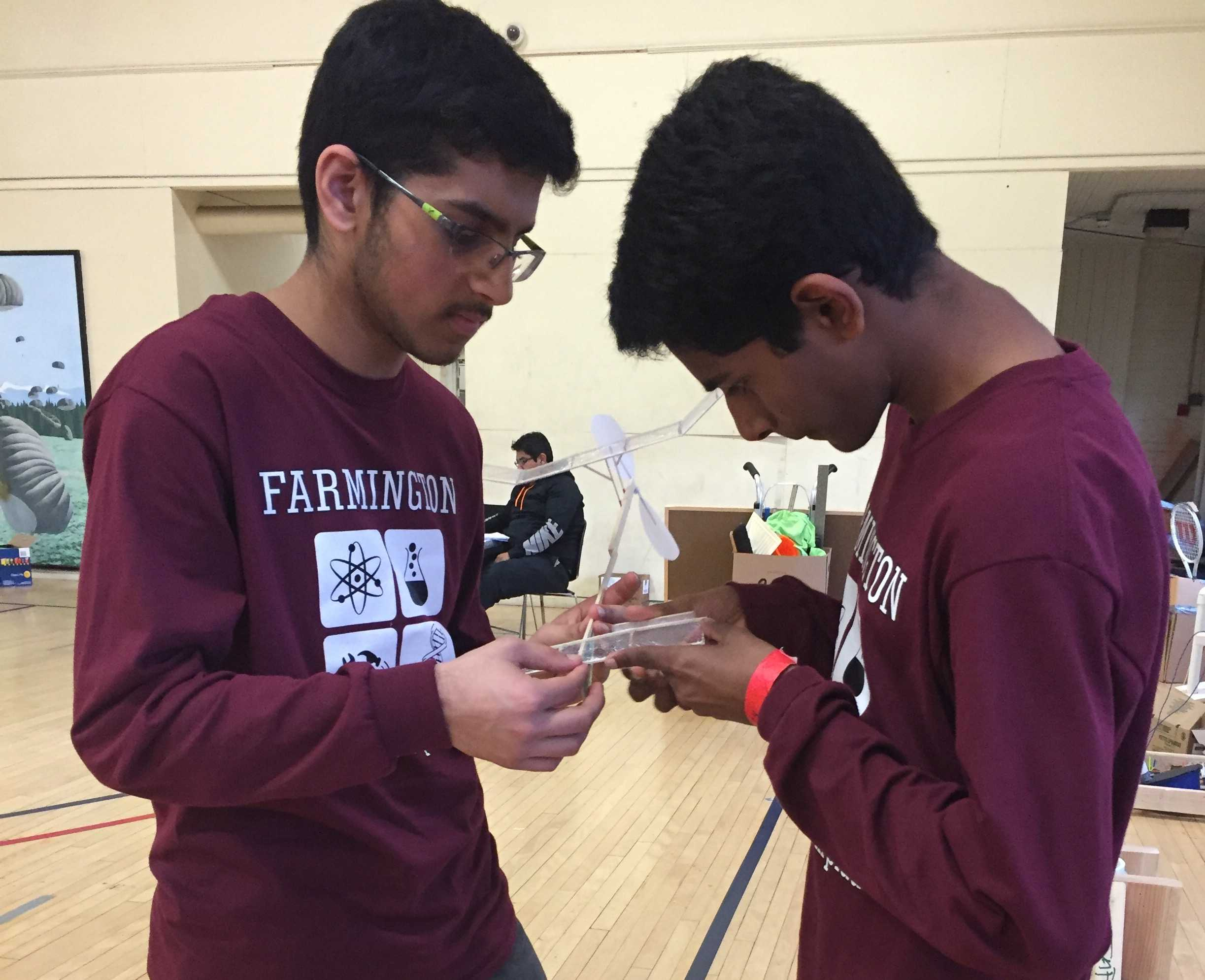 Preparing for takeoff-- Sophomore Amir Suhail and freshman Vishanth Palanivel file down the wings on the rubber band-powered plane prior to the competition for the event Wright Stuff. The duo launched their plane and was scored on the amount of time that it spent in the air. They placed seventh out of the teams that competed in this event.