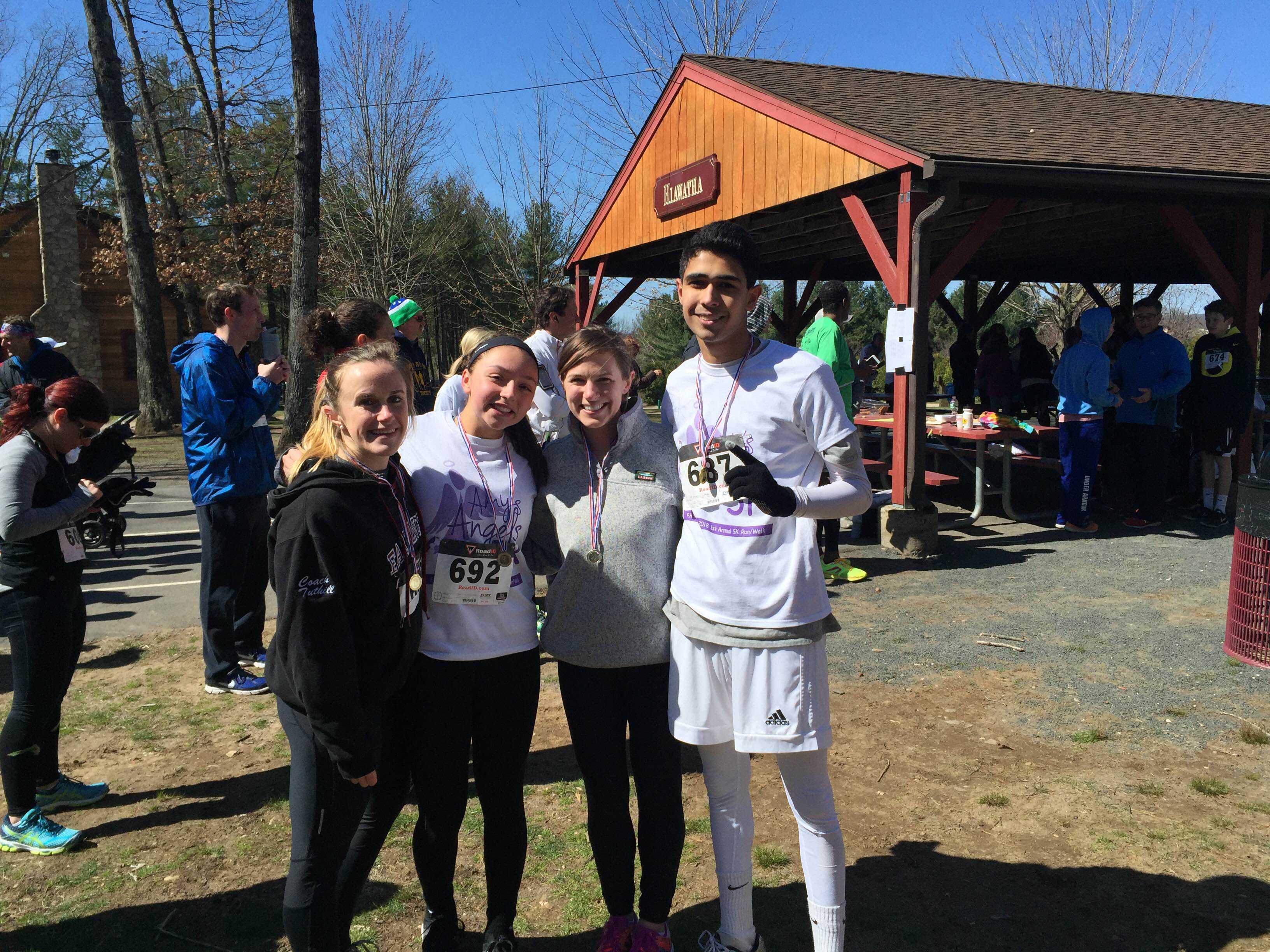 Sophomores Vini Munshi and Olivia Bottalico show off their medals alongside social studies teacher Emma Tuthill and English teacher Katie Buckley after running the 5K on April 10.