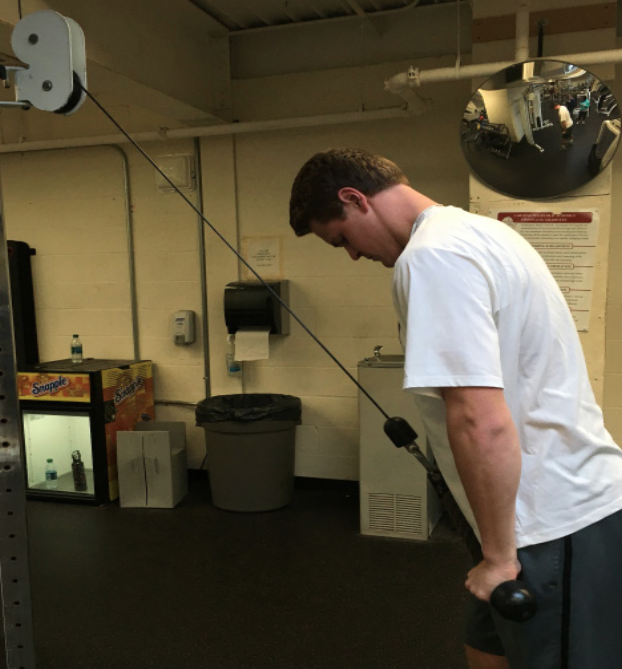 Pumping iron-- Students begin preparing for their upcoming sports seasons, using the weight room in order to get back in shape. Senior Max Ruh strength- ens his arms using the cable crossover machine to improve his performance in the upcoming spring lacrosse season.
