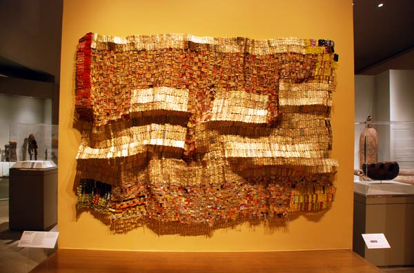 "West African wall art-- ""Between Earth and Heaven"" is a metal tapestry that can be viewed at the Metropolitan Museum of Art. West African artist El Anatsui created the art with techniques both traditional and modern."