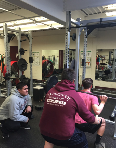 Breathe in, exhale out--Junior Matt Lynch squats as junior Murphy Gruninger and Coach Jay Mendoza spot him during a club meeting after school. The club began meeting in early January.