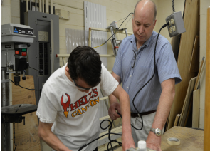 All in the wrist-- Construction teacher Richard Mulcunry assists senior Jace Firth in sanding and smoothing out a portion of his project. Mulcunry plans on spending time with his family and working on his personal business.