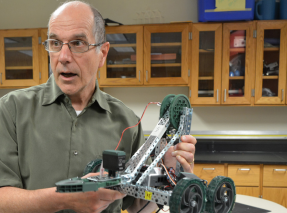 Driving force-- Science teacher Vincent Tokarz reviews and demonstrates the mechanics of a student made motorized project in his third period Engineering class. Tokarz will miss students and his fellow colleagues.