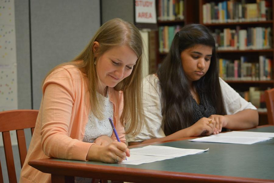 English teacher Kaitlin McIntyre and sophomore Nazish Shakeel look over student writing.