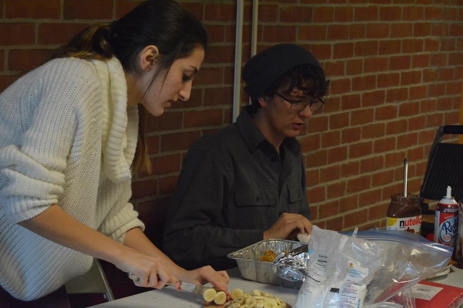 Pass the Nutella-- Seniors Noor Taweh and Hunter Caouette make crepes for students in teachers in the morning before classes start. Crepes were sold all week as part of National French Week to spread awareness for the culture.