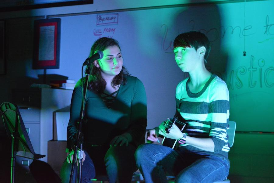 """Sing me a song-- Junior Rita Monahan (left) and senior Sarah Davis (right) sing """"Here Comes a Thought"""" by Rebecca Sugar at the annual Acoustic Night on December 9. Acoustic Night is a yearly event that is hosted by the Gay Straight Alliance."""