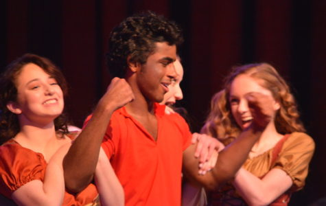 Arms of steel-- Senior Ashish John (Gaston) shows off his muscles to his admirers, junior Rebekah Moses (Silly Girl), junior Sarah Rahmig (Silly Girl) and sophomore Quinn Mahoney (Silly Girl). The girls try to swoon him into marrying one of them instead of senior Catherine Mackay (Belle).