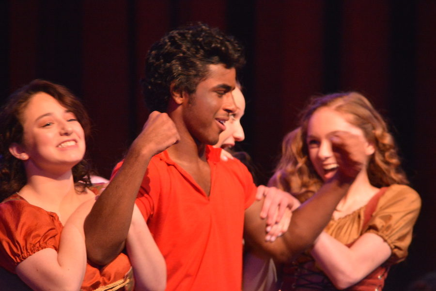 Arms+of+steel--+Senior+Ashish+John+%28Gaston%29+shows+off+his+muscles+to+his+admirers%2C+junior+Rebekah+Moses+%28Silly+Girl%29%2C+junior+Sarah+Rahmig+%28Silly+Girl%29+and+sophomore+Quinn+Mahoney+%28Silly+Girl%29.+The+girls+try+to+swoon+him+into+marrying+one+of+them+instead+of+senior+Catherine+Mackay+%28Belle%29.