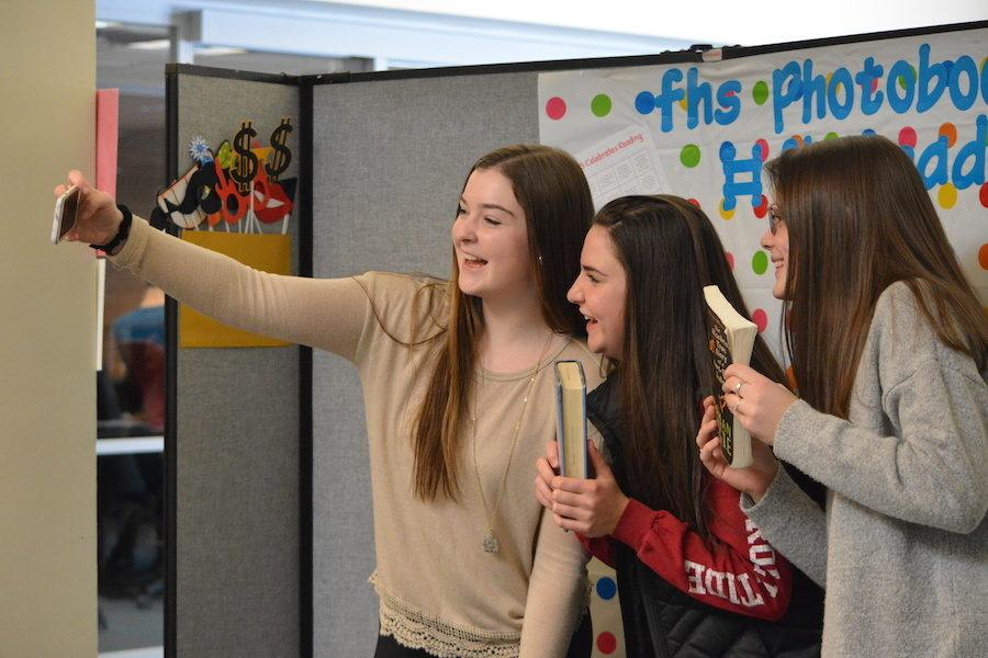 """Juniors Bella Podgorski and Anna Green pose with freshman Johanna Wolkoff for a selfie in the library. The backdrop, which reads """"FHS reads"""", was put up for students to take pictures in front of as part of the Week Long Love of Reading celebration from March 13 to 17."""