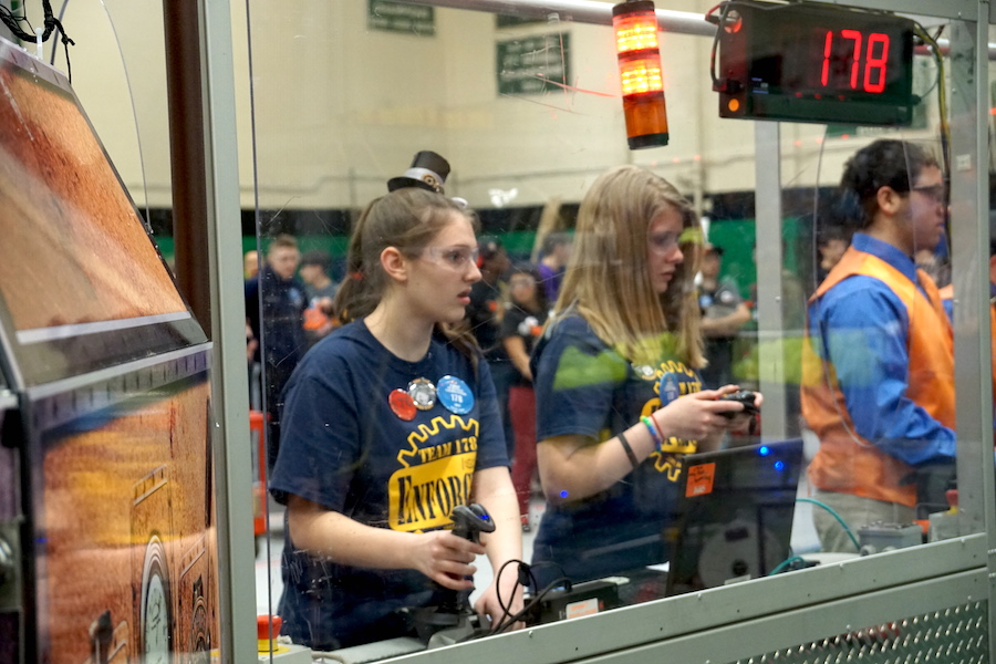 Hands up-- Senior Jamie Poole (right) and freshman Emma Nollman (left) drive their robot during one of their semifinal matches. The team made it to the finals with the help from their alliance partners, Sim-City (Simsbury, Connecticut) and Bobcat Robotics (South Windsor, Connecticut).