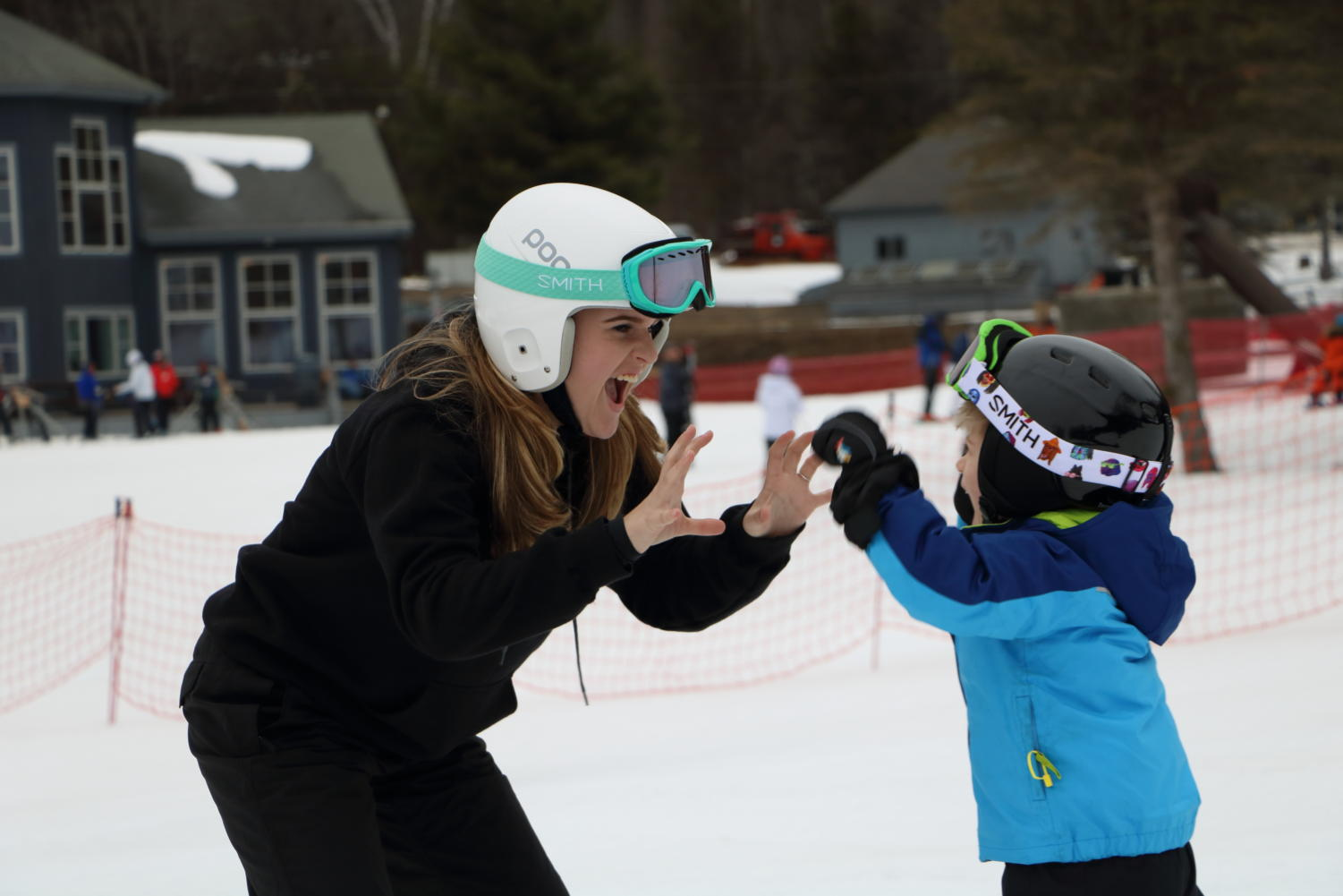 Success in the snow-- Senior Avery Laberge congratulates a young skier during a lesson. Lessons are between one hour and one hour and a half, and anyone from the ages three and older can participate.