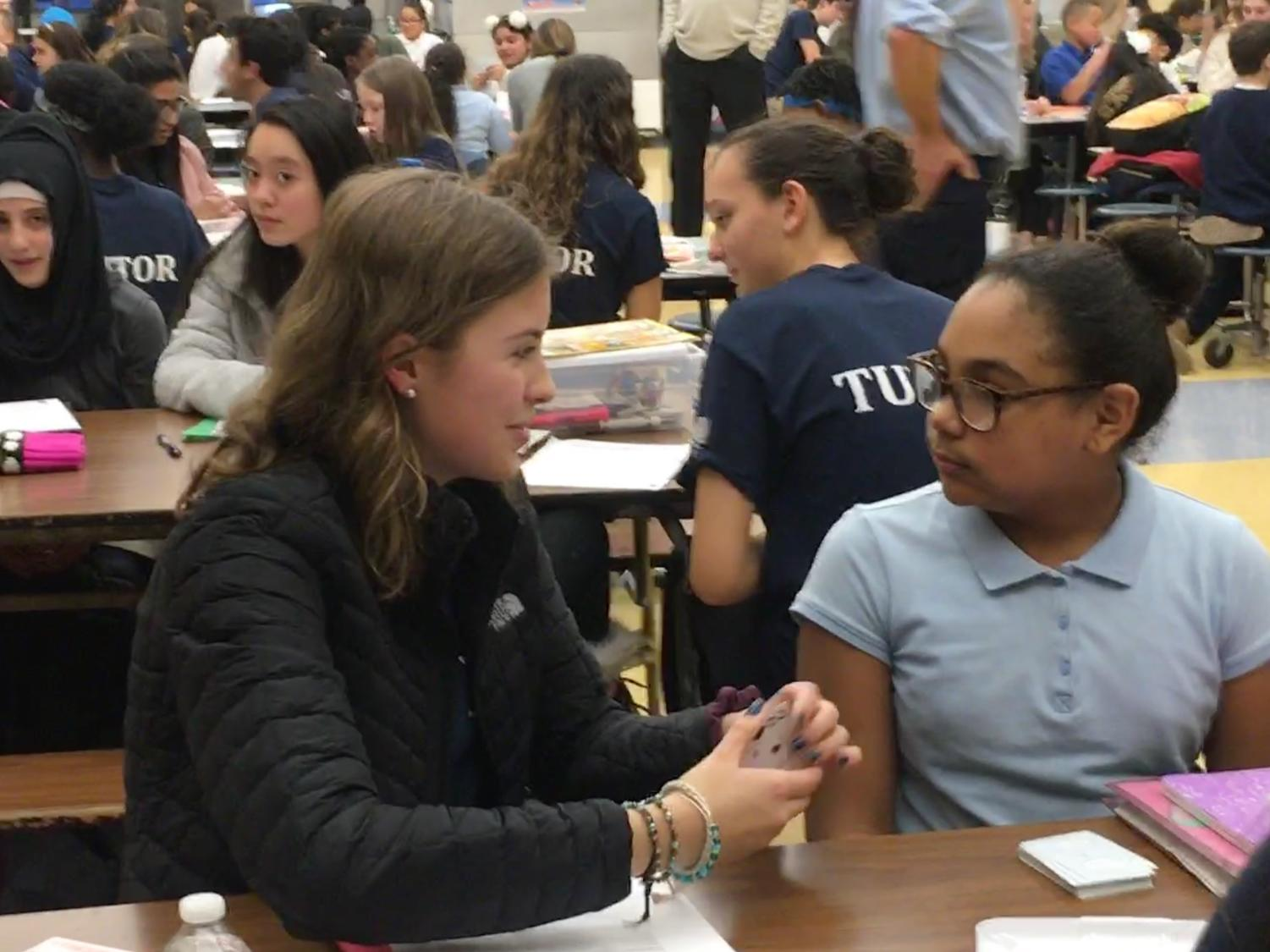 Here to help--Sophomore Maddy Jobin gets to know her assigned student from Vance Elementary during the first tutoring session. Students from the high school volunteer on thursdays after school to tutor at the elementary school.