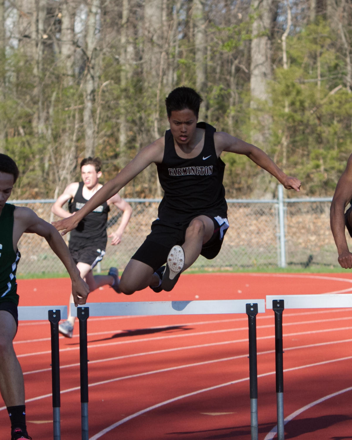 Hurdling over the competition-- Senior Mark Kang leaps over a hurdle during one of last years meets. Although he has no plans to run track in college, this senior is still keeping an open mind.
