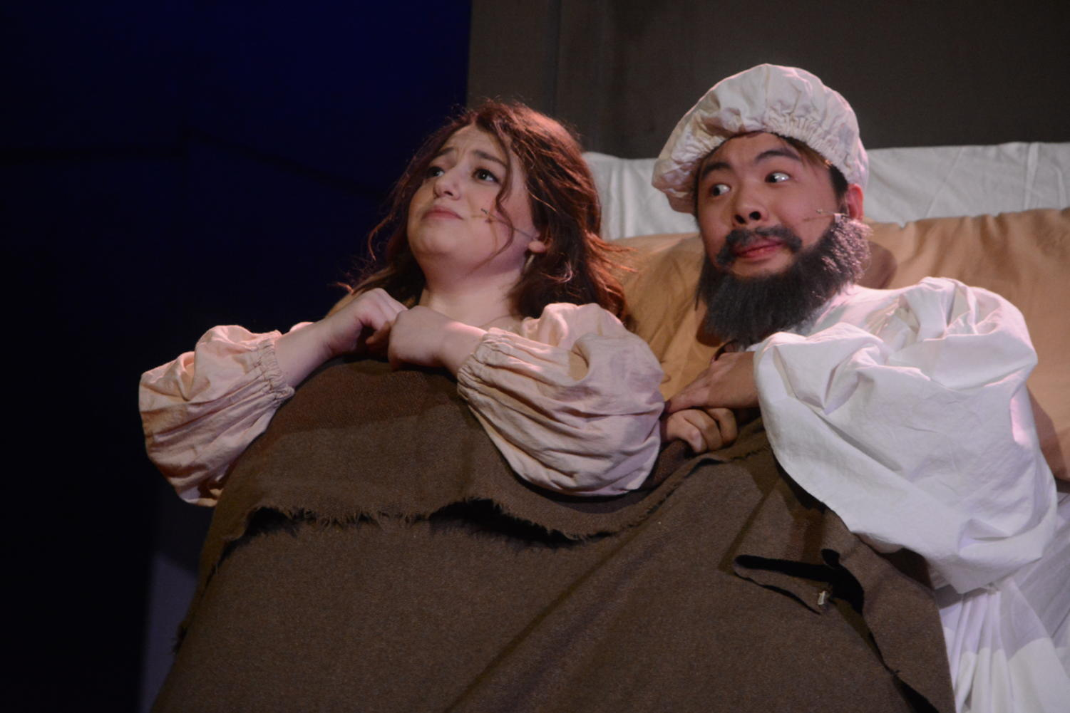 A change of heart-- In a humorous scene from the Drama Department's production of Fiddler on the Roof, Golde, played by senior Rebekah Moses (right), decides that her daughter should marry the town tailor, Motel, to the secret elation of Tevye (left), played by junior Tristan Wong. The cast performed on March 8, 9, and 10 after missing dress rehearsals due to snow.