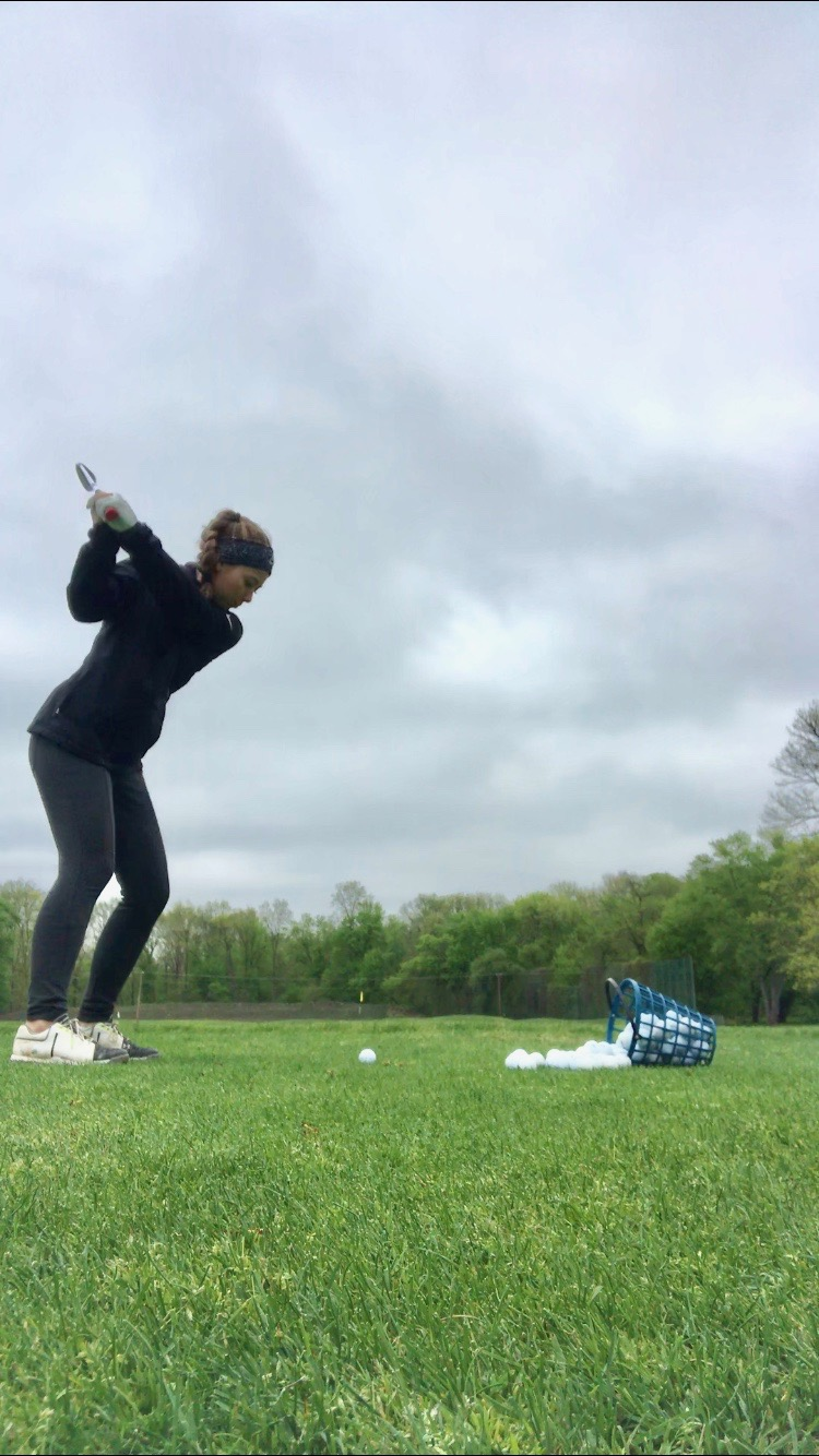 Swinging into the tournament-- Junior captain Mia Grzywinski gets some extra practice in despite the gloomy weather. The golf team finished the regular season with a 9-3 record.