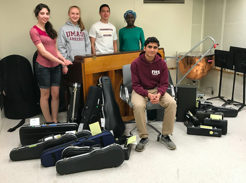 Music to our ears -- Juniors Rohit Limaye (front), Praise Adeloka (left), Kevin Gabree (center left), Anita Ghodsi (right), and senior Sarah Rahmig smile for a photo with some of the instruments obtained by the recent musical instruments drive. The project, spearheaded by Limaye, collected 30 to 40 instruments, which will soon be distributed to elementary-aged students.