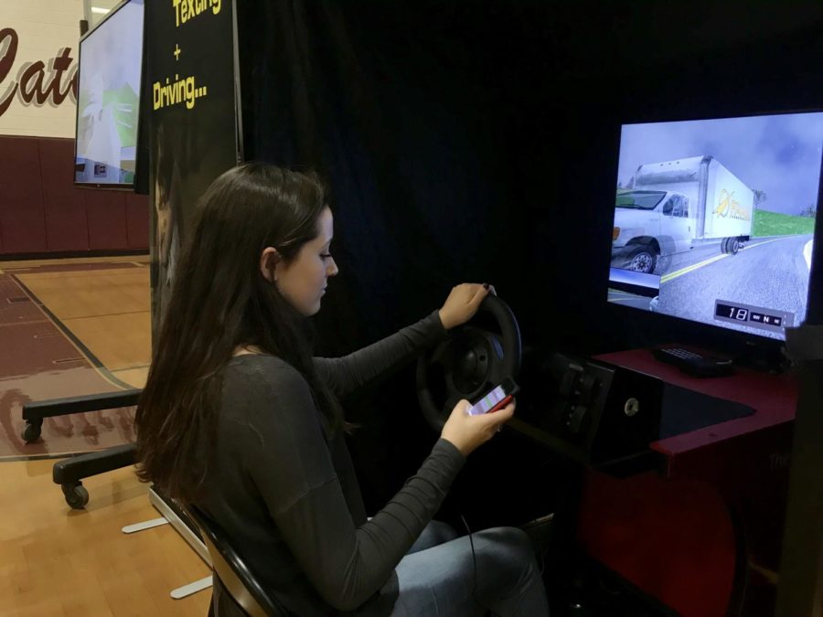 Texting+Teen+--+Senior+Paige+Walsh+focuses+on+texting+away+while+participating+in+the+distracted+driving+simulation.+The+distracted+driving+assembly+took+place+on+October+5+in+place+of+period+2.%0A