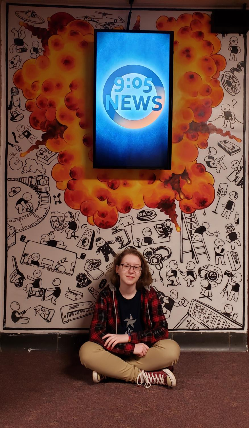 Artistic force--Sophomore Yana Tsyvis sits in front of the mural she completed that is located outside the Edge Media room. The mural took many weeks to complete.