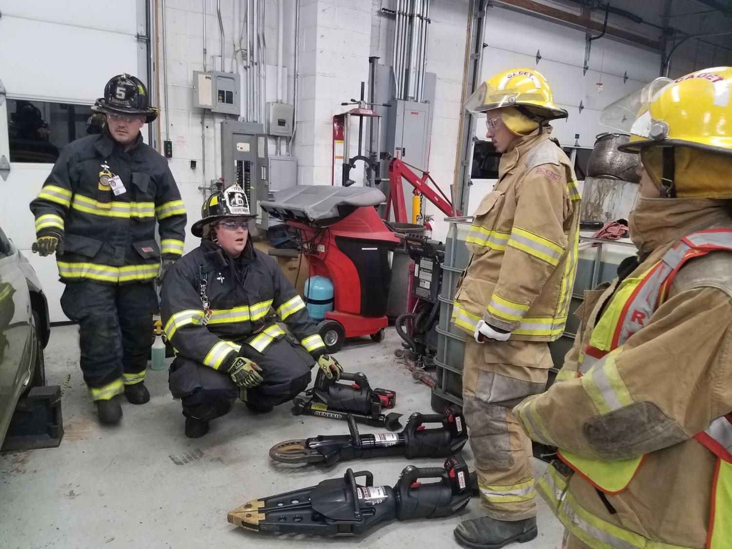 Firefighters in training-- Fire cadets (in black) and firefighters (in tan) prepare for a vehicle extrication drill. The Farmington Fire Cadets is a program that trains prospective high schoolers interested in a firefighting career.
