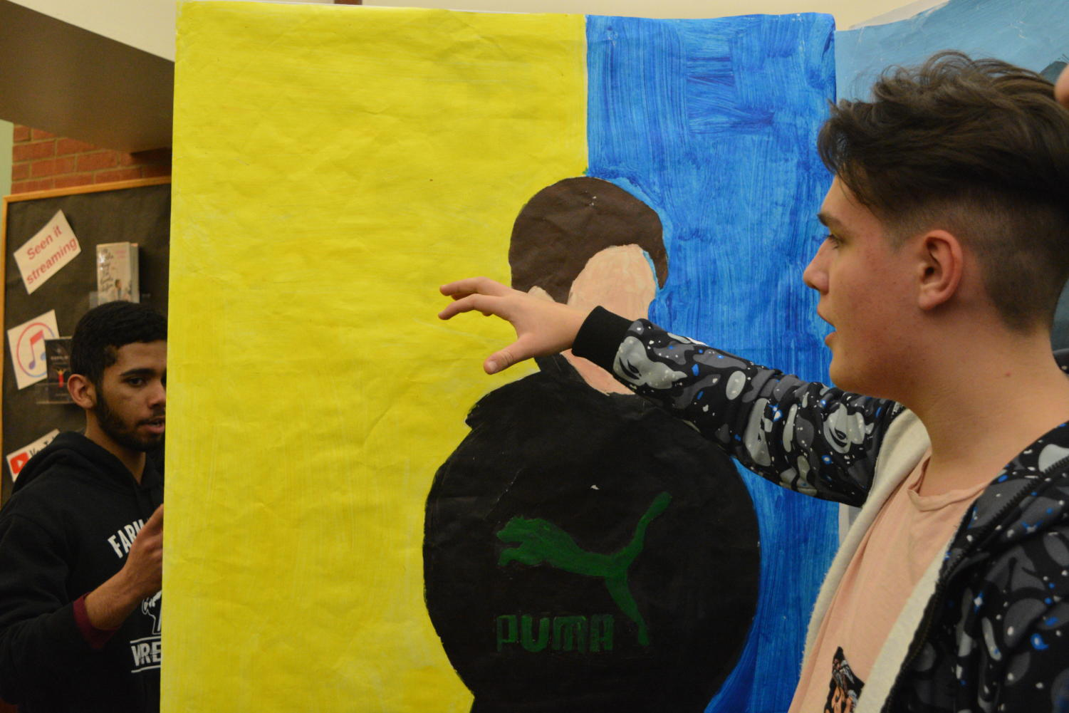 Explaining Emotions-- Freshman Maksym Ievsiev gives a presentation on his acrylic painting. After the ESOL students gave their presentations, they participated in multiple workshops given by local artists.