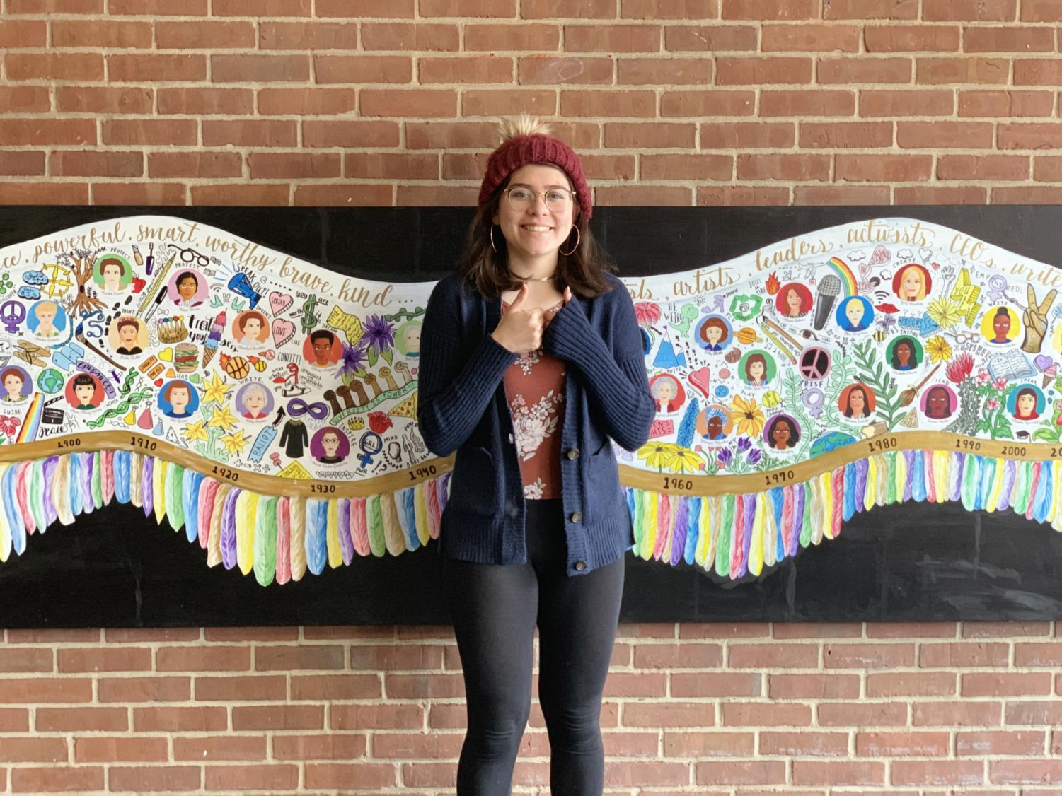 Spreading my wings-- Junior Sophie Shack smiles for a picture in front of a mural she designed for her Government and Law class. The project features 30 famous women and can be found in the alcove near the library and cafeteria. Viewers can center themselves between the wings and become a part of the narrative.