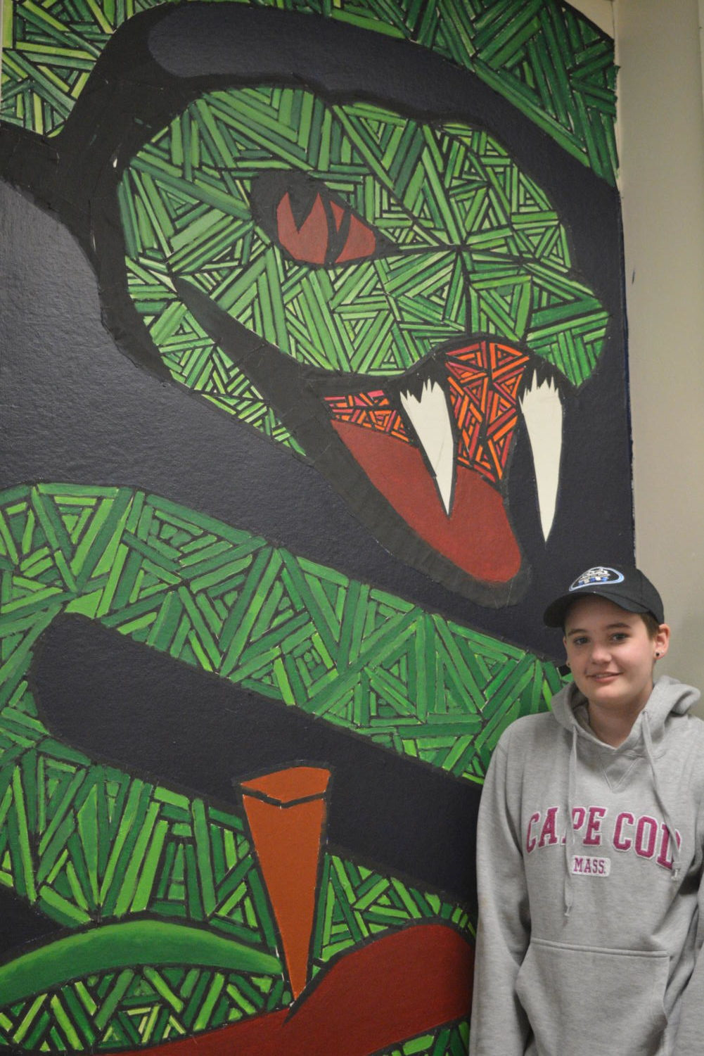 Picture perfect-- Junior Emma Fink poses in front of her serpent mural in the art wing. Fink has loved art ever since she was four years old, and prefers drawing and sketching.