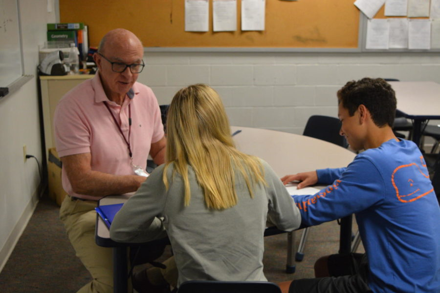 Math is hard-- Math tutor Jake Auger works with students in the Math Tutorial. Auger has been working at the high school for the last 10 years and is retiring this year.