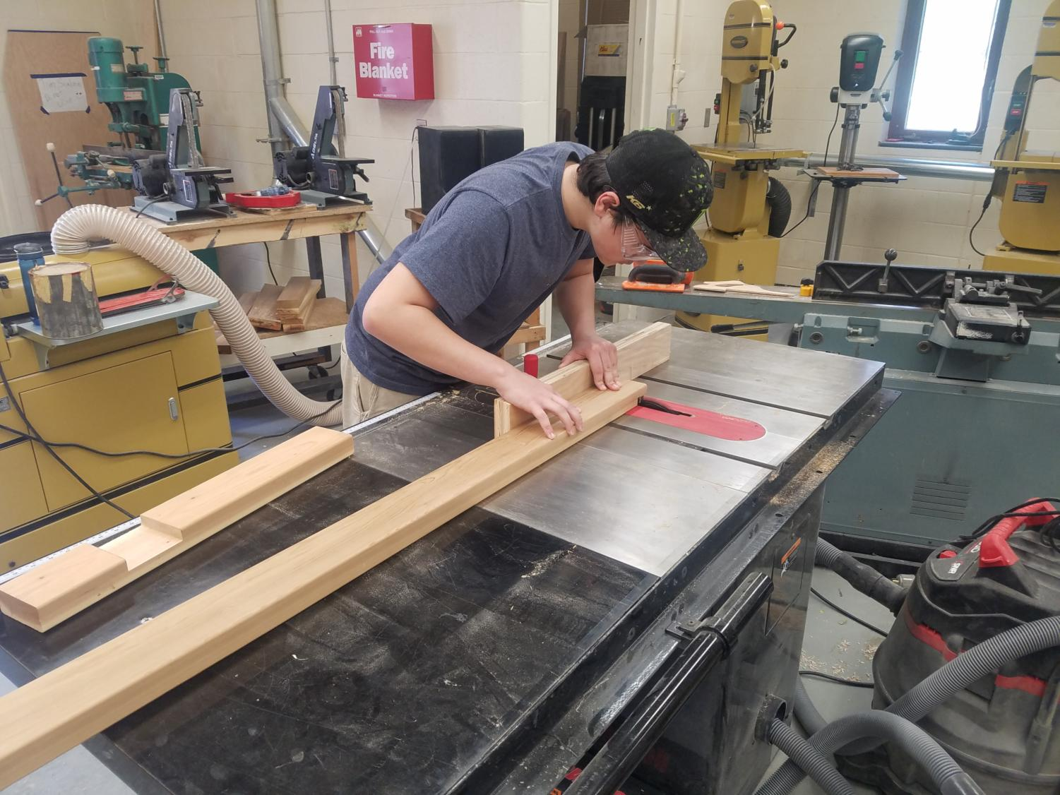 In loving memory-- Senior Joe Kall works on creating a memorial bench in memory of the late Department Leader of Library, Media and Technology K-12 Martha Burr. Kall completed the bench as part of his Custom Capstone project.