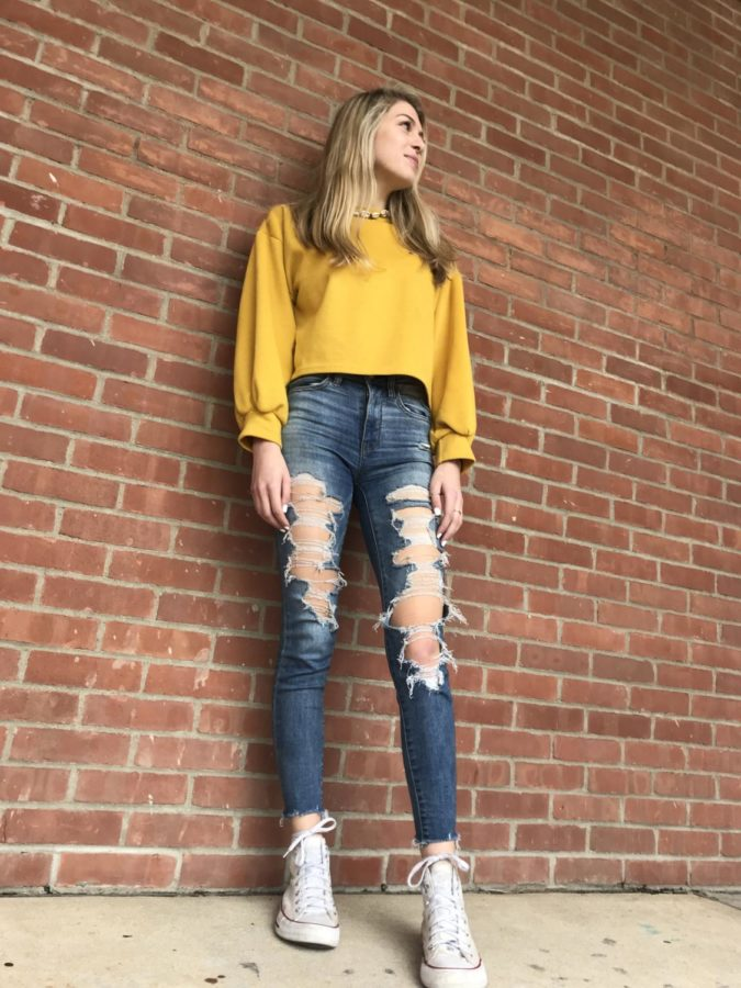 Camera Ready-- Sophomore Victoria Prusaczyk looks camera ready with her yellow long-sleeved crop top, blue ripped jeans and classic high top white converse. Converse, among many others, are a popular shoe choice amongst girls at the high school.