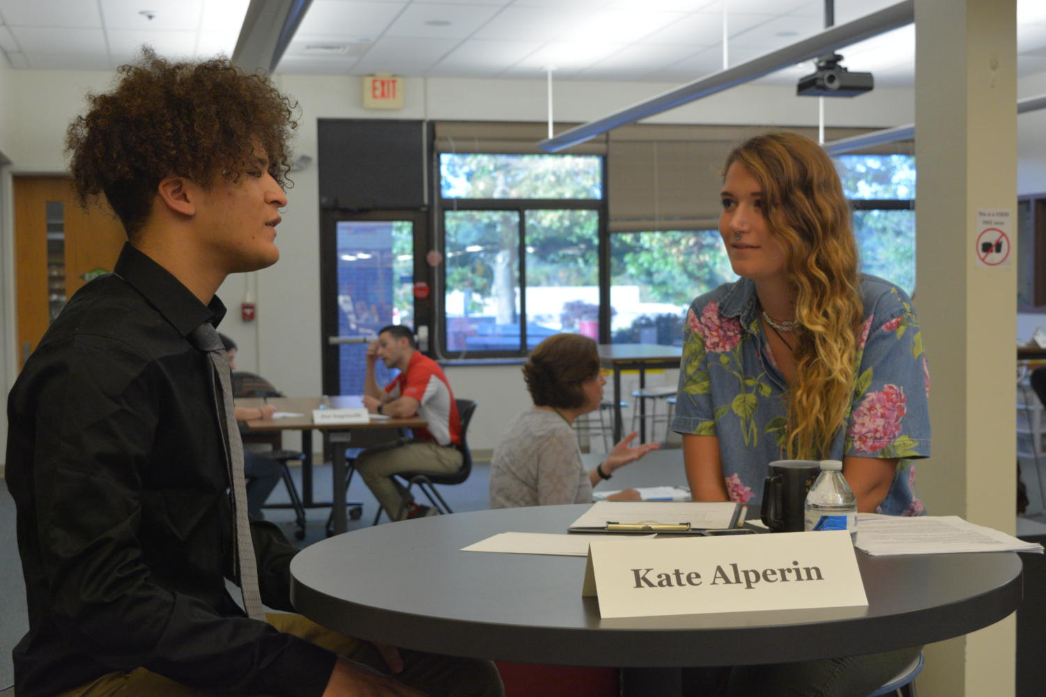 How do you do?-- Senior Luis Baez(left), who is enrolled in the Social Justice and Equity Capstone, speaks with high school alumna Katie Alperin (right) about his project. The Capstone Networking Event took place in the library on September 24 and 25.
