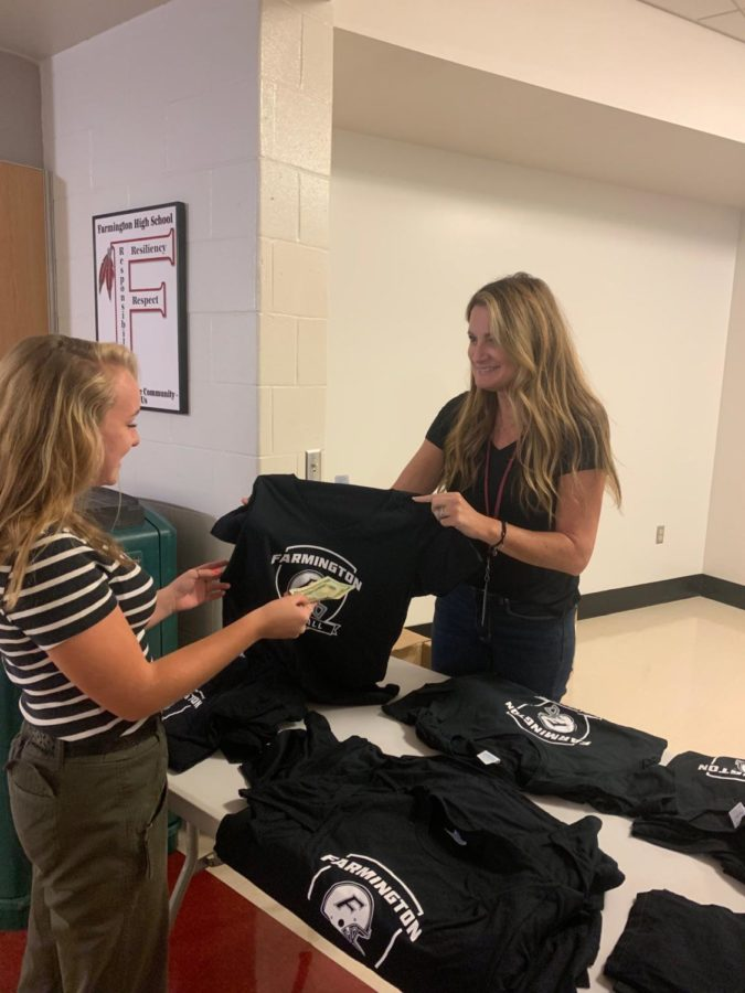 Get+them+while+they%E2%80%99re+hot+--+Sophomore+Lily+Taylor+purchases+a+Blackout+t-shirt+from+Trish+Guglielmo%2C+mother+of+senior+captain+Mitch+Guglielmo.+All+students+are+encouraged+to+wear+black+to+the+game+on+Friday%2C+October+4+against+Wethersfield.+