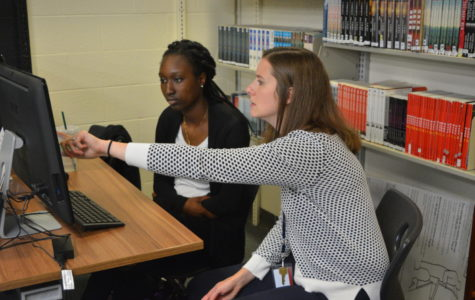 Ready to write-- Senior Daphne Dibgolongo receives help with her writing from Writing Fellowship teacher Shea Benton-Reger. The writing center is located under the stairs in the school library.