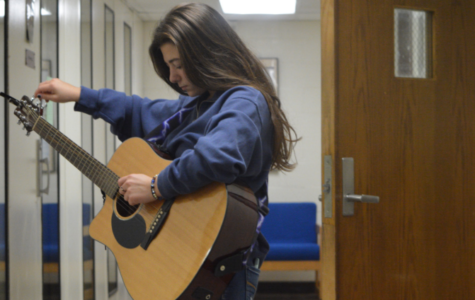 Tuning up-- Senior Zoe Cozentino adjusts her strings before taking the stage at the Senior Cafe. This years Senior Cafe took place on October 25, and featured numerous performances by students throughout the school.