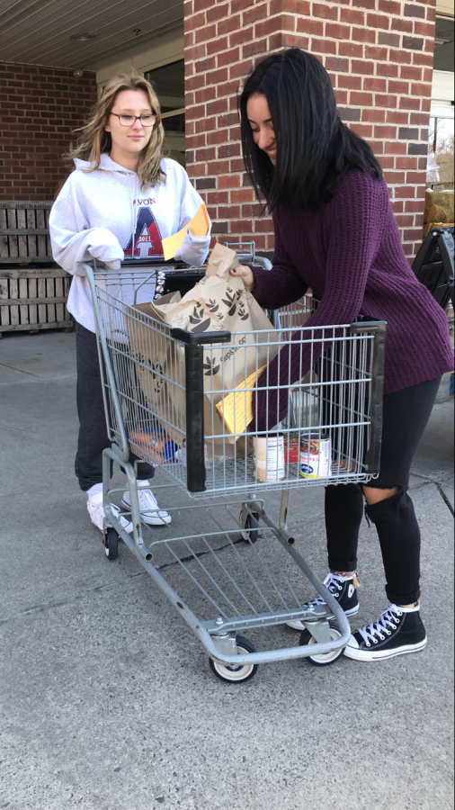 Lending a hand-- Juniors Taylor Ellef (left) and Jayda Argulles (right) collect donations for the Farmington Police Department Food Drive. The food was delivered to families in Farmington on November 23.