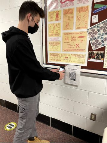 Scanning-- Senior Ricky Podgorski scans a new QR code to check into the bathroom. The codes were added outside of every bathroom in the school in order to improve contact tracing.