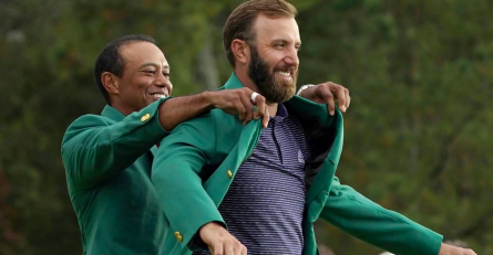 Fits Like a Glove--Defending champion Tiger Woods places the green jacket on 2020 winner Dustin Johnson. The victory marks Johnson's second major championship and first Masters.
