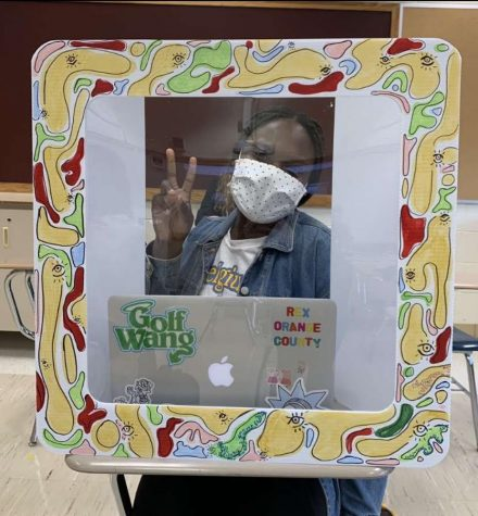 Pose for a picture -- Senior Mercy Adekola sits at her desk personalized safety shield. Senior Lindsay Fielder decorates her classmates shields to bring art into classrooms.