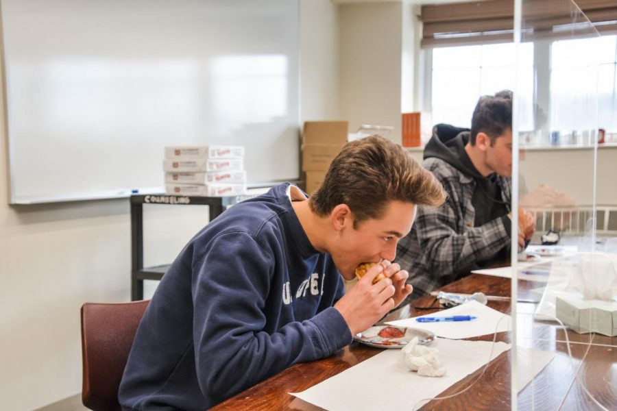 Food for thought-- Senior John Guerrera taste tests a grinder during The Voice's annual food review. For this year's review, Guerrera  helped to determine whether Naples, George's, Claudia's or Frankline Ave. had the best chicken parm grinder.