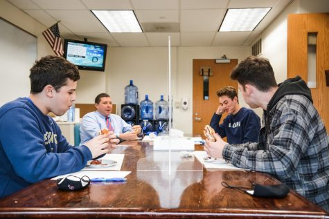 Bites of happiness-- Seniors Hollis Tharpe (left front), Ricky Podgorski (right front), John Guerrera (right back) and Principal Scott Hurwitz (left back) taste test  chicken parm grinders in a blind taste test. Claudia's Grinder Shop was declared the winner, beating out Naples, George's, and Franklin Ave. Grinder Shop. The grinders were assessed on their freshness, sauce to cheese ratio, structural integrity, and chicken quality.