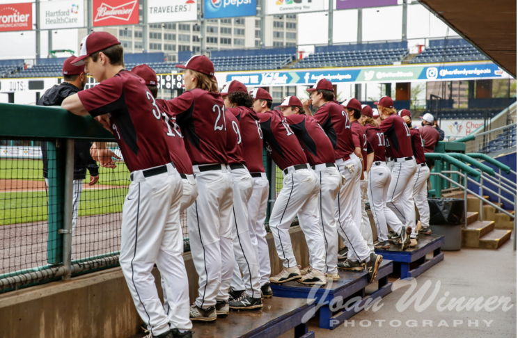 In the big leagues  — The Farmington baseball team lines up in the dug out of Dunkin Donuts Park in Hartford. Farmington beat Avon 9-2 with the support of a student section.