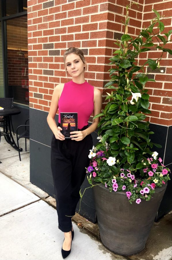 Published and proud -- Author Khrystyna Stets poses with a copy of her novel, Faded Reality. Stets is a senior enrolled in the custom capstone.