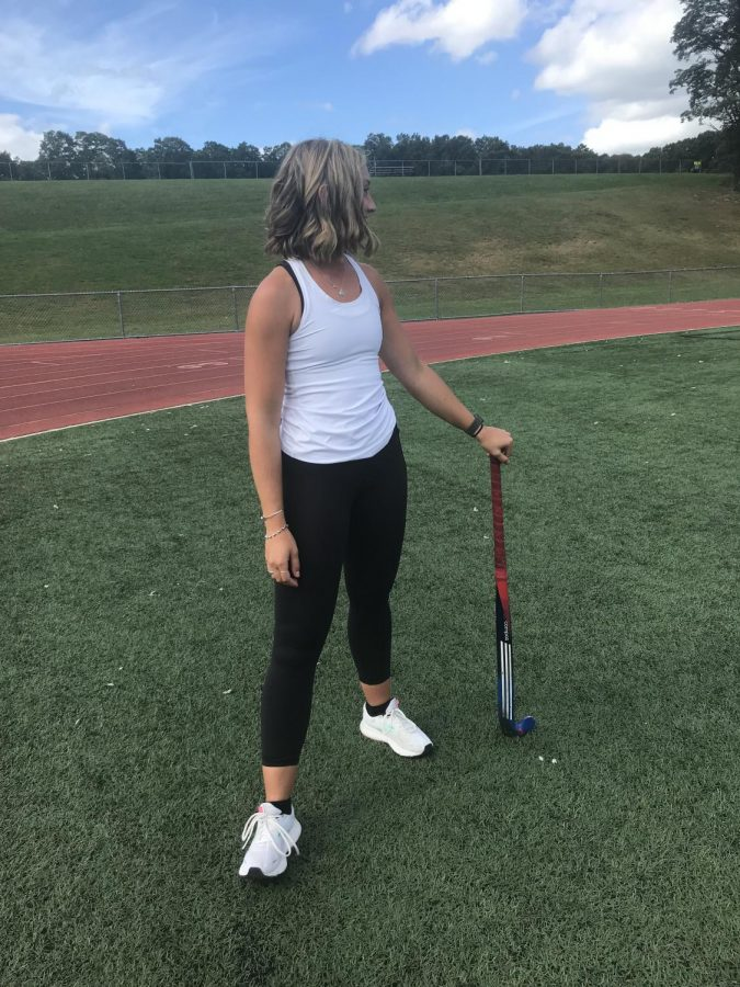 Welcome -- Head field hockey coach Sadie Robinson overlooks the team warmup before leading practice. Robinson joins the River Hawks after eight years as a player and five years as a coach.
